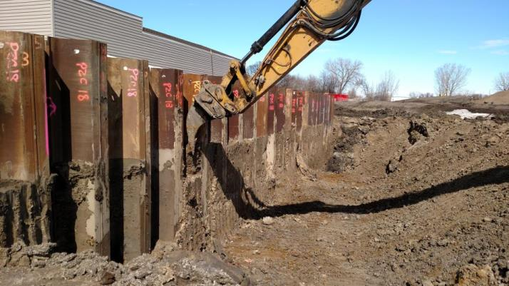 Scraping mud from sheet piling